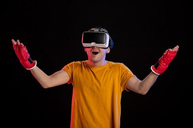 Młody mężczyzna gra w wirtualną rzeczywistość w rękawiczkach mma na ciemnej powierzchni