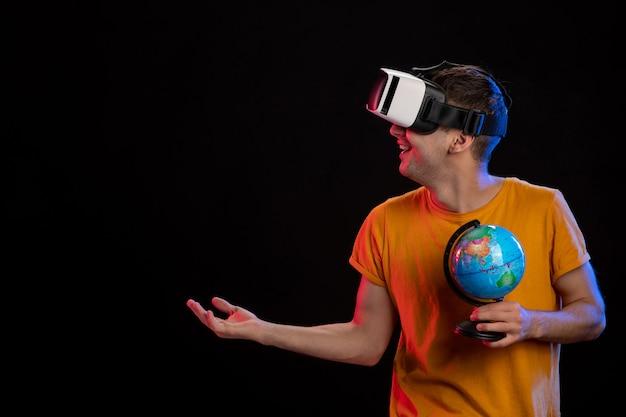 Młody mężczyzna gra w wirtualnej rzeczywistości, trzymając kulę ziemską na ciemnej powierzchni