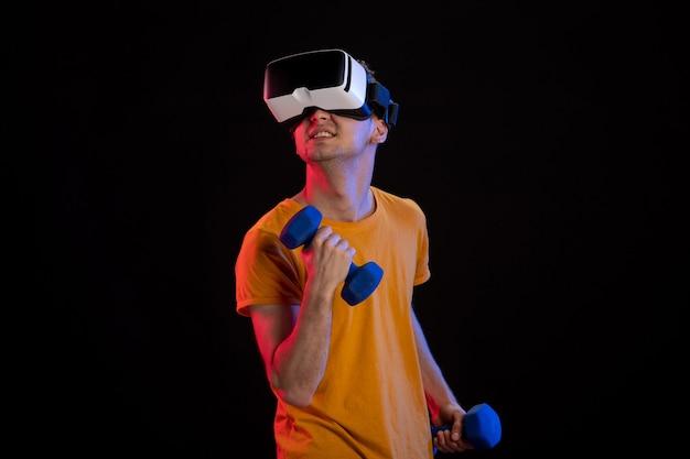 Młody mężczyzna gra wirtualnej rzeczywistości z hantlami na ciemnej powierzchni