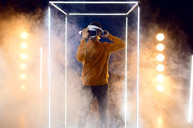 Młody mężczyzna gra za pomocą zestawu słuchawkowego rzeczywistości wirtualnej i gamepada w świecącej kostce