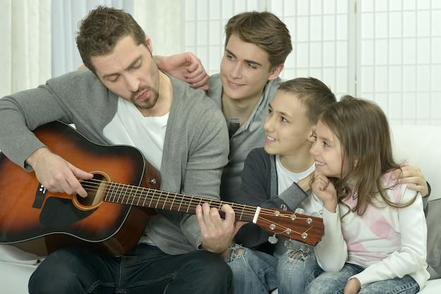 Młody mężczyzna grający na gitarze dla swojej rodziny