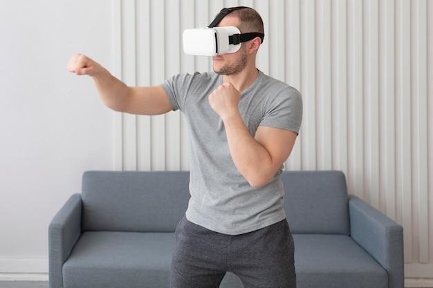 Młody mężczyzna grający w gry wideo mając na sobie okulary wirtualnej rzeczywistości