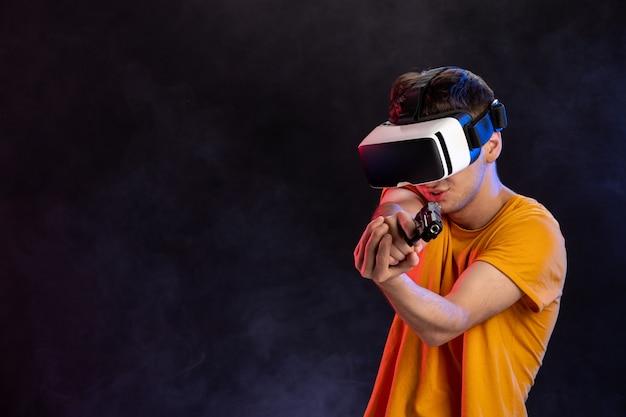 Młody mężczyzna grający w wirtualną rzeczywistość z pistoletem na ciemnym wideo technicznym o grach