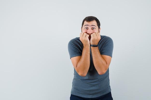 Młody mężczyzna gryzie emocjonalnie pięści w szarym t-shircie i wygląda na przestraszonego