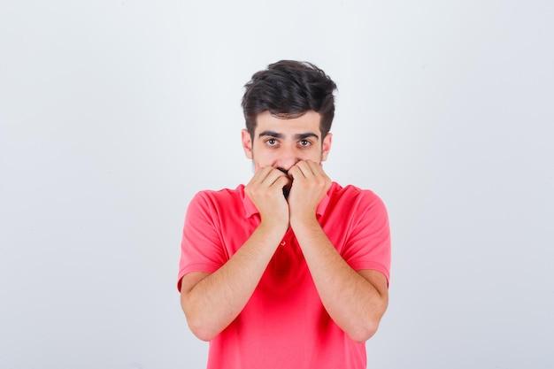 Młody mężczyzna gryzie pięści emocjonalnie w różowej koszulce i wygląda na przestraszonego. przedni widok.