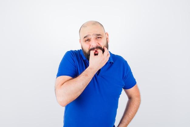 Młody mężczyzna gwizduje podczas pozowania w t-shirt i wyglądający uroczo. przedni widok.