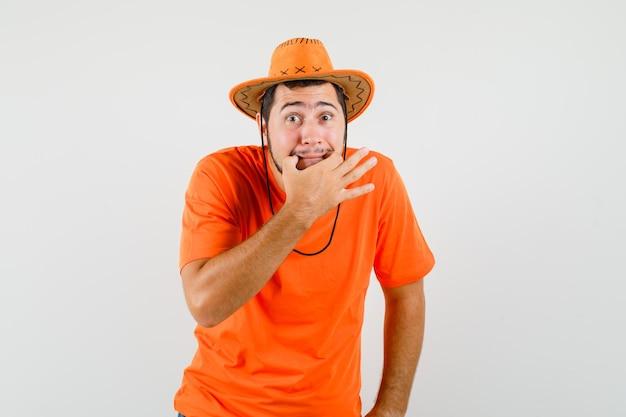 Młody mężczyzna gwizduje w pomarańczowym t-shirt, kapeluszu i niespokojnym wyglądzie. przedni widok.