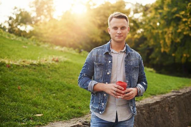 Młody mężczyzna hipster stojący z kawą na wynos w parku, uśmiechając się uprzejmie do kamery. szczęśliwy beztroski przystojny facet w niebieskiej dżinsowej kurtce