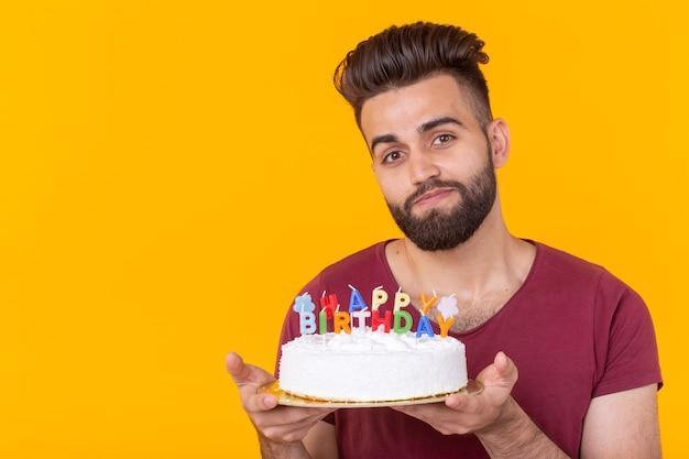 Młody mężczyzna hipster z brodą trzymający tort z napisem gratulacje urodzinowe z okazji rocznicy i święta. koncepcja promocji i zniżek. skopiuj miejsce