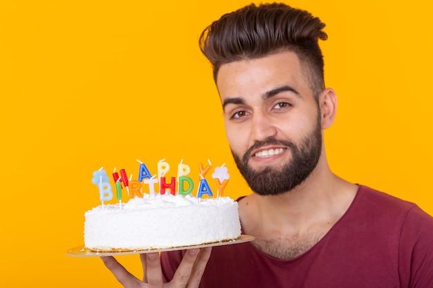 Młody mężczyzna hipster z brodą trzymający tort z napisem gratulacje urodzinowe z okazji rocznicy i święta. koncepcja promocji i zniżek.