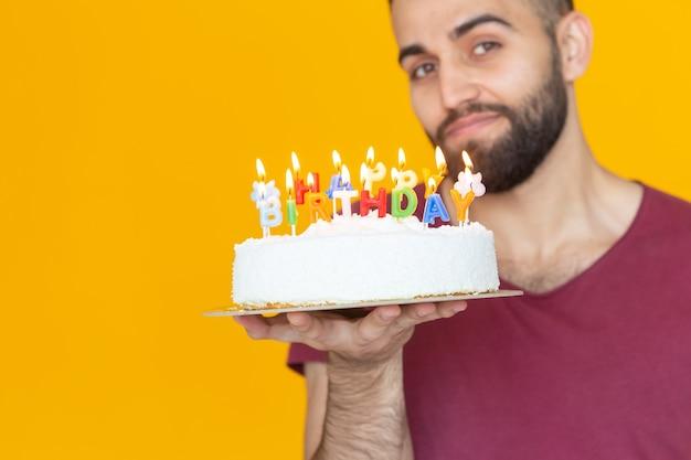Młody mężczyzna hipster z brodą trzymający tort z napisem gratulacje z okazji urodzin