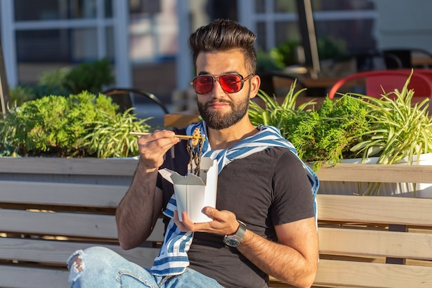 Młody mężczyzna hipster z wąsami i brodą je chińskie kluski z drewnianymi pałeczkami z białego pudełka na lunch. koncepcja kuchni azjatyckiej.