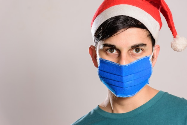 Młody mężczyzna hispanic ubrany w maskę i kapelusz santa na białym tle