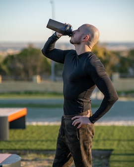 Młody mężczyzna hiszpanie wody pitnej po treningu w boisku sportowym