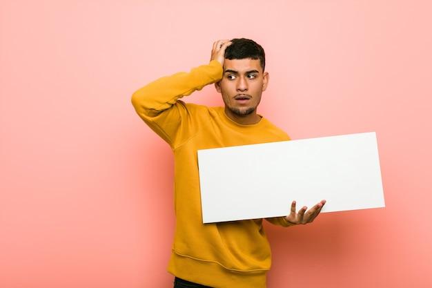 Młody mężczyzna hiszpanin trzyma tabliczkę