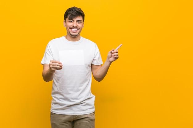 Młody mężczyzna hiszpanin trzymając tabliczkę uśmiechnięty radośnie, wskazując palcem wskazującym z dala.