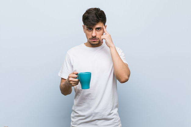 Młody mężczyzna hiszpanin trzymający kubek, wskazując palcem na skroń, myśląc, skupiony na zadaniu.