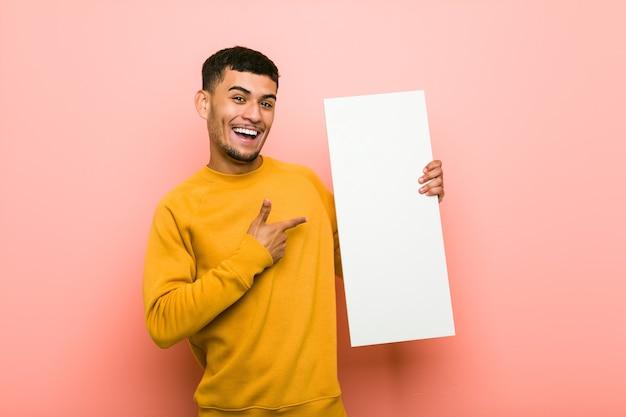 Młody mężczyzna hiszpanin trzymający tabliczkę