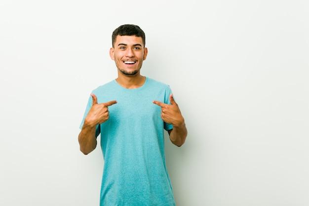 Młody mężczyzna hiszpanin zaskoczony wskazując palcem, uśmiechając się szeroko.