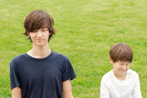 Młody mężczyzna i chłopiec uprawiają jogę na świeżym powietrzu. nastolatek siedzi w pozycji lotosu na zielonej trawie. skopiuj miejsce miejsce na tekst. szkolenie rodzinne