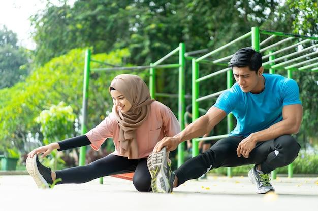 Młody mężczyzna i dziewczyna w chuście wykonują razem ćwiczenia rozgrzewkowe przed ćwiczeniami w parku