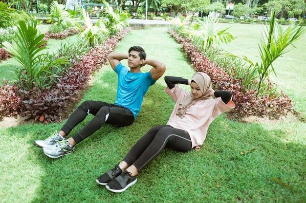 Młody mężczyzna i dziewczyna w chuście wykonują ruch, aby razem ćwiczyć mięśnie brzucha podczas ćwiczeń na świeżym powietrzu w parku
