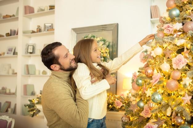Młody mężczyzna i jego córka dekorowanie choinki