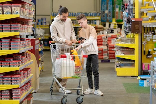 Młody mężczyzna i jego nastoletni syn odwiedzają nowoczesny supermarket z artykułami żelaznymi
