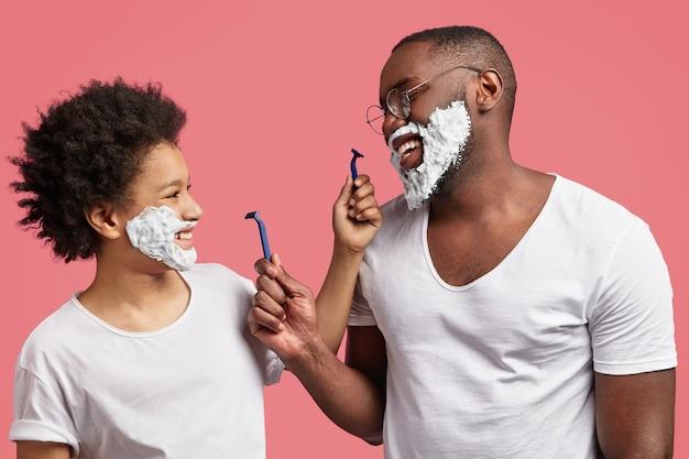 Młody mężczyzna i jego syn mają piankę do golenia na twarzy i trzymają brzytwy