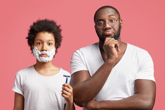 Młody mężczyzna i jego syn z kręconymi włosami, trzymając brzytwę