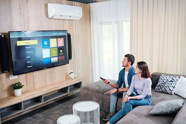 Młody mężczyzna i jego żona wybierają coś do oglądania na cyfrowym wyświetlaczu panelu plazmowego telewizora podczas odpoczynku w domu