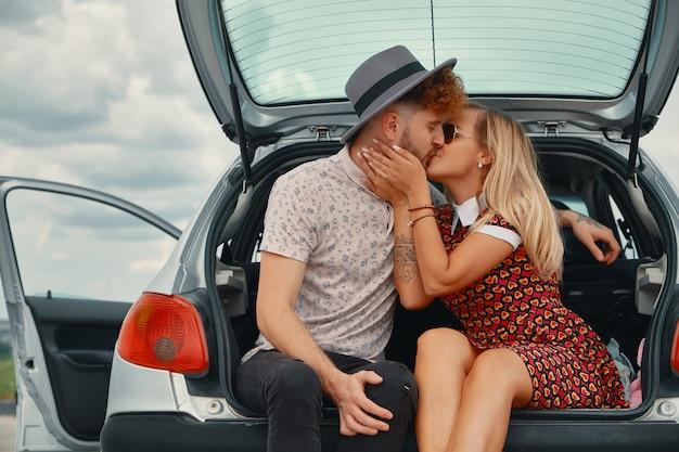 Młody mężczyzna i kobieta całuje w bagażniku samochodu