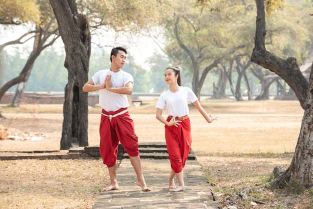Młody mężczyzna i kobieta ćwiczą tradycyjny taniec tajski