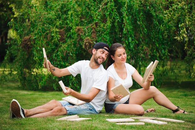 Młody mężczyzna i kobieta gra w gigantyczne domino w parku na trawie.