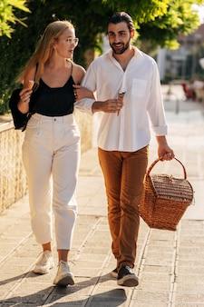 Młody mężczyzna i kobieta idą do parku na piknik