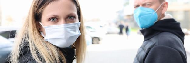 Młody mężczyzna i kobieta idąc ulicą w maskach ochronnych