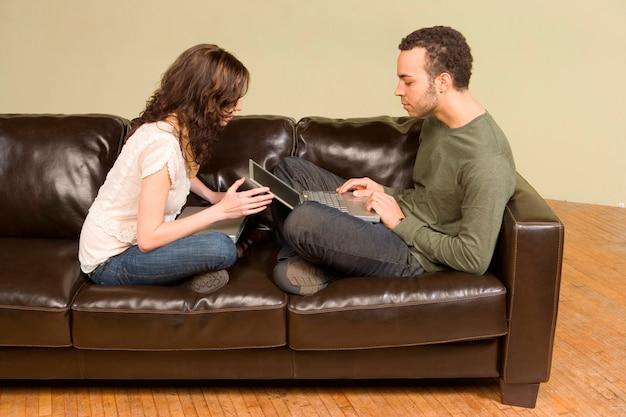 Młody mężczyzna i kobieta, informatyka na kanapie