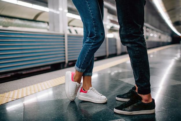 Młody mężczyzna i kobieta korzystają z podziemia. para w metrze. wytnij widok mężczyzny i kobiety stojących przed sobą. szybki pociąg. pod ziemią. historia miłosna. walentynki.