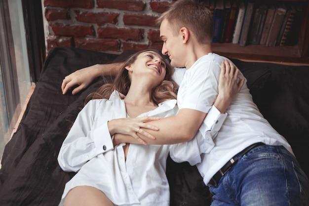 Młody mężczyzna i kobieta leżą w łóżku i bawią się