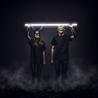 Młody mężczyzna i kobieta mają na sobie czarne ubrania i maski królika i kota, a nad nimi świeci się światło