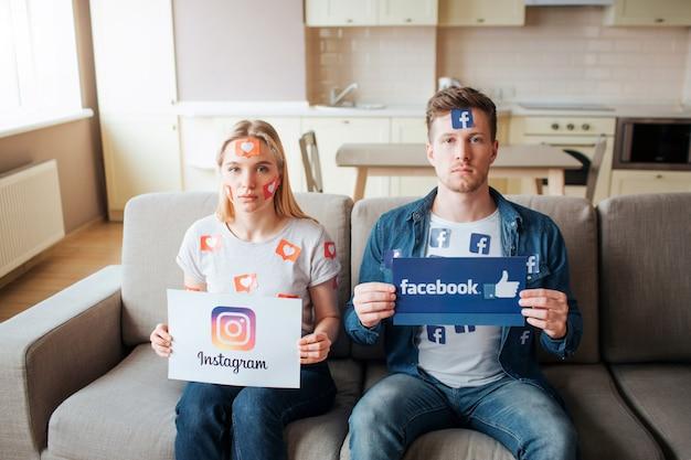Młody mężczyzna i kobieta mają uzależnienie od mediów społecznościowych. uzależniający ludzie patrzą w kamerę. trzymając logo. życie na instagramie.