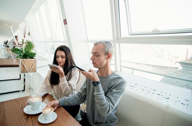 Młody mężczyzna i kobieta na randce w kawiarni. para siedzi w kawiarni i robi zdjęcia filiżankom flat white lub cappuccino. koncepcja mediów społecznościowych. mężczyzna i kobieta biorąc zdjęcie napojów.
