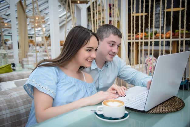 Młody mężczyzna i kobieta, patrząc na laptopa w kawiarni