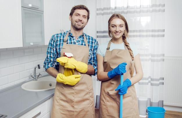 Młody mężczyzna i kobieta pozują w fartuchach z artykułami gospodarstwa domowego w jasnej kuchni