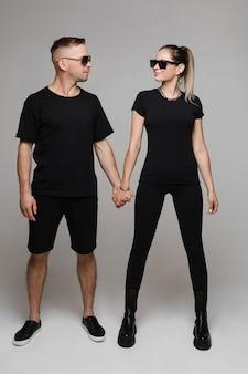 Młody mężczyzna i kobieta rasy kaukaskiej, patrząc na siebie i uśmiechając się, trzymając się za ręce. koncepcja mody