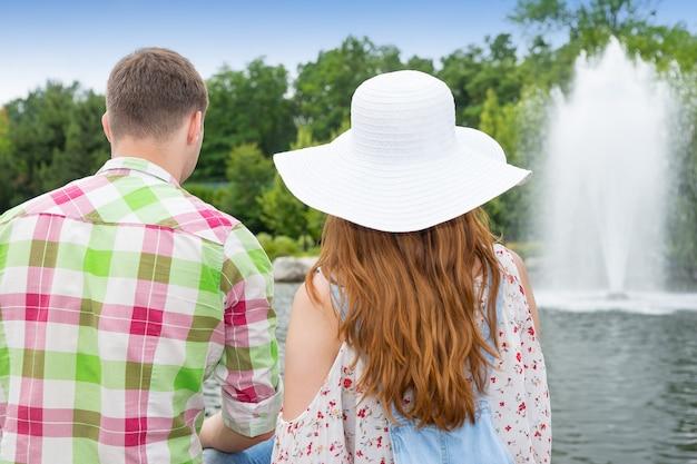 Młody mężczyzna i kobieta siedzą naprzeciwko sztucznego jeziora w parku z fontanną i różnymi drzewami w tle