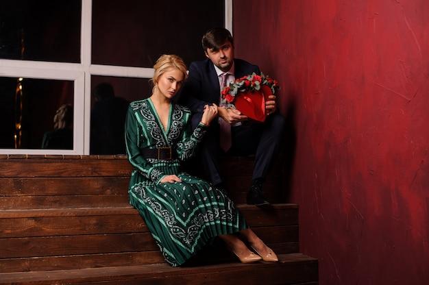 Młody mężczyzna i kobieta siedzi na schodach z bukietem kwiatów