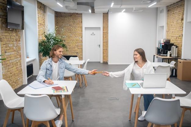 Młody mężczyzna i kobieta siedzi przy stołach i przygotowuje się do zdania egzaminu