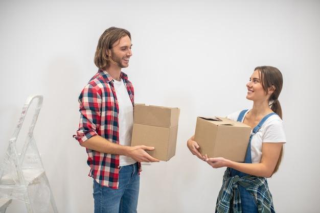Młody mężczyzna i kobieta stojąca blisko ściany z pudełkami w rękach