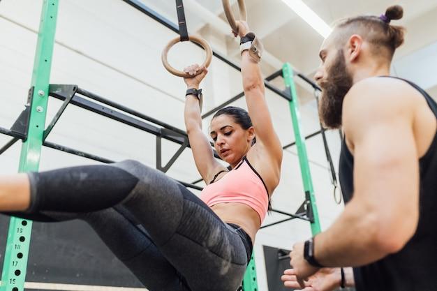 Młody mężczyzna i kobieta szkolenia toghether siłownia gimnastyczne pierścienie